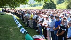People pray near coffins