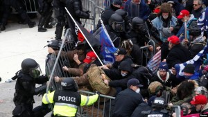 Pro-Trump protesters tear down a barricade as they clash with Capitol Police
